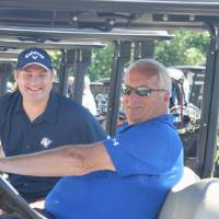 two football alumni in a golf cart